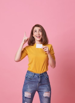 Podekscytowana młoda kobieta pokazując punkt karty kredytowej i dłoni w przestrzeni kopii izolowanych ponad różowym.