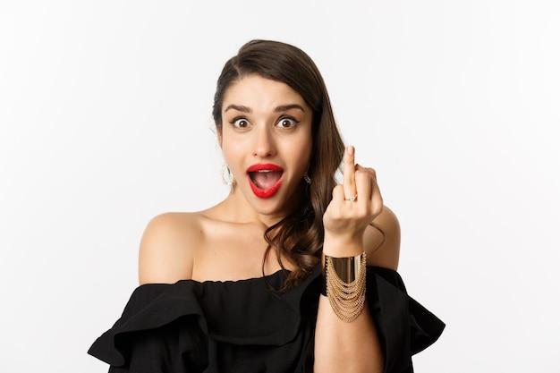 Podekscytowana młoda kobieta pokazująca palec z pierścionkiem zaręczynowym, zaręczyła się, powiedziała tak, stojąc na białym tle