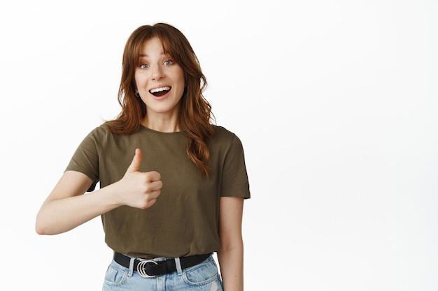 Podekscytowana młoda kobieta pokazuje kciuki w górę i uśmiecha się radośnie, daje pozytywne opinie, zachwycona czymś fajnym, chwali jakość, mówi tak, jak dobry produkt, stoi na białym