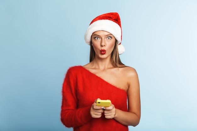 Podekscytowana młoda kobieta ubrana w świąteczny kapelusz, przy użyciu telefonu komórkowego.