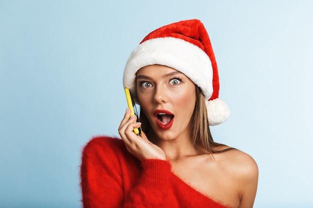 Podekscytowana młoda kobieta ubrana w świąteczny kapelusz, rozmawia przez telefon komórkowy.