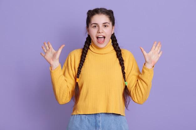 Podekscytowana młoda kobieta ubrana w żółty sweter, ma dwa warkocze, pozujące przed liliową ścianą
