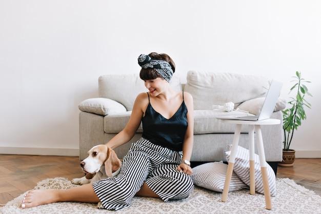 Podekscytowana młoda kobieta w pasiastych spodniach siedzi na podłodze obok sofy i laptopa bawi się ze zwierzakiem