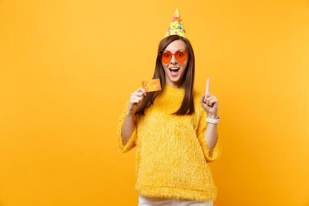 Podekscytowana młoda kobieta w pomarańczowych okularach serca, urodziny kapelusz wskazujący palec wskazujący w górę, trzymając kartę kredytową świętuje, ciesząc się wakacjami na białym tle na żółtym tle. ludzie szczere emocje, styl życia.