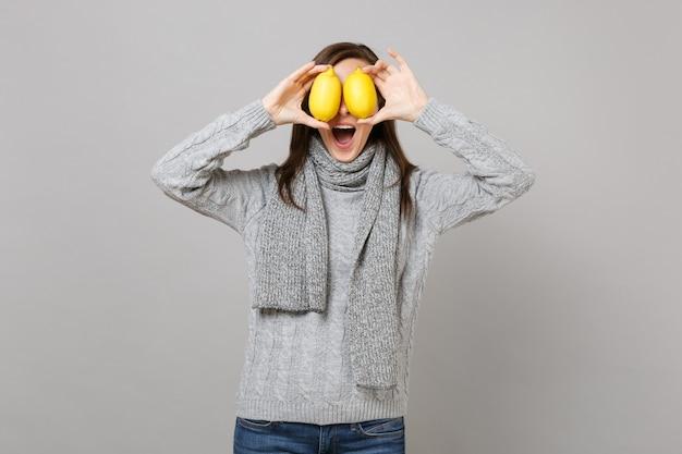 Podekscytowana młoda kobieta w szarym swetrze, szalik zakrywający oczy z cytrynami na białym tle na szarym tle w studio. zdrowy styl życia moda, szczere emocje ludzi, koncepcja zimnej pory roku. makieta miejsca na kopię.