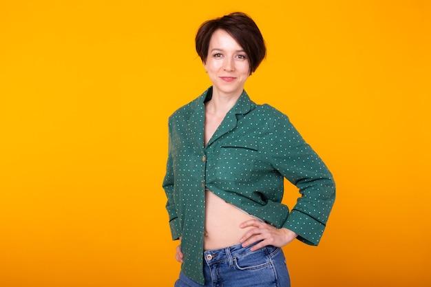 Podekscytowana młoda kobieta w zielonym stroju domowym, szeroko uśmiechnięta, dobrze się bawiąca. na białym tle na żółtym tle