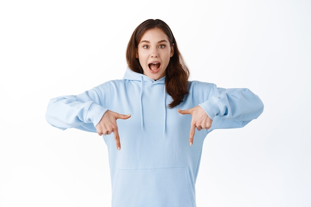 Podekscytowana młoda kobieta wskazuje palcami w dół i krzyczy z radości, pokazując niesamowitą ofertę promocyjną, demonstrując reklamę na przestrzeni kopii, stojąc nad białą ścianą