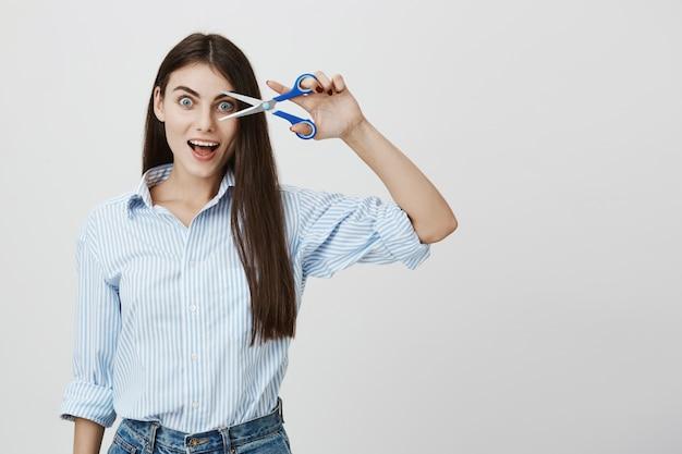 Podekscytowana młoda kobieta z długimi włosami pokazuje nożyczki