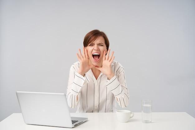 Podekscytowana młoda, krótkowłosa brunetka dama podnosi ręce do ust i marszczy brwi, krzycząc głośno, pozując na biało w formalnym stroju