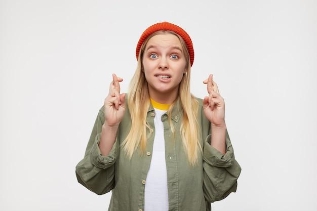 Podekscytowana młoda, ładna białogłowa kobieta z przypadkową fryzurą, która z zaskoczeniem unosi brwi i gryzie niepokojąco dolną wargę podczas krzyżowania palców, odizolowana na niebiesko