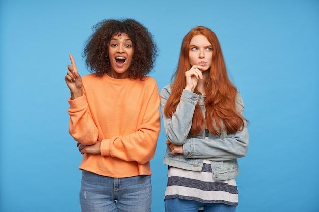 Podekscytowana młoda, ładna brązowowłosa ciemnoskóra kobieta podnosi palec wskazujący z gestem pomysłów, pozując nad niebieską ścianą ze swoim zdziwionym rudym przyjacielem