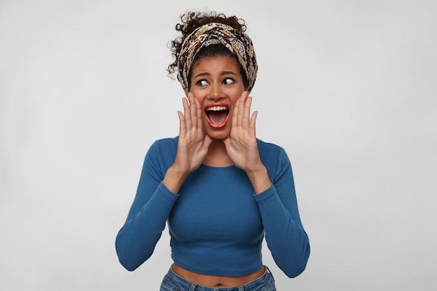 Podekscytowana młoda ładna brunetka ciemnoskóra kobieta z zebranymi włosami, trzymając podniesione ręce w pobliżu ust, krzycząc z otwartymi ustami, odizolowaną na białym tle