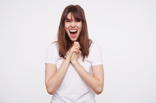 Podekscytowana młoda ładna ciemnowłosa kobieta trzymająca podniesioną rękę pod brodą i krzycząca z szeroko otwartymi ustami, pozująca na białej ścianie w zwykłych ubraniach