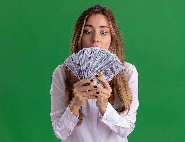 Podekscytowana młoda ładna kaukaska dziewczyna trzyma i patrzy na pieniądze odizolowane na zielonej ścianie z miejscem na kopię