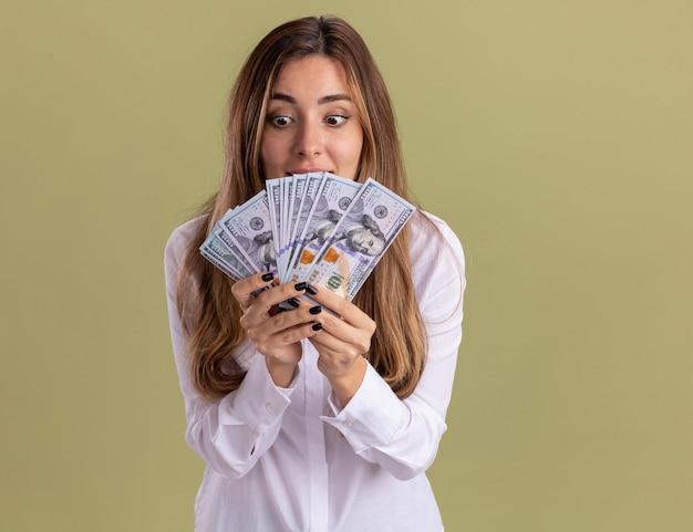Podekscytowana młoda ładna kaukaska dziewczyna trzyma i patrzy na pieniądze