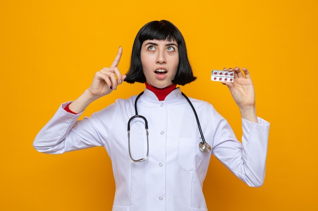 Podekscytowana młoda ładna kaukaska dziewczyna w mundurze lekarza ze stetoskopem trzymająca opakowanie pigułki i wskazująca w górę