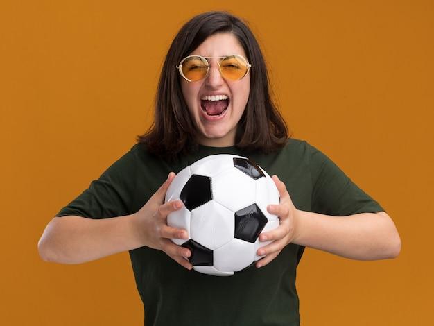 Podekscytowana młoda ładna kaukaska dziewczyna w okularach przeciwsłonecznych trzymająca piłkę odizolowaną na pomarańczowej ścianie z miejscem na kopię