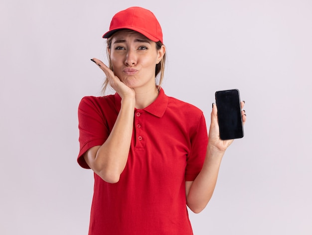Podekscytowana młoda ładna kobieta dostawy w mundurze kładzie rękę na brodzie i trzyma telefon na białym tle na białej ścianie