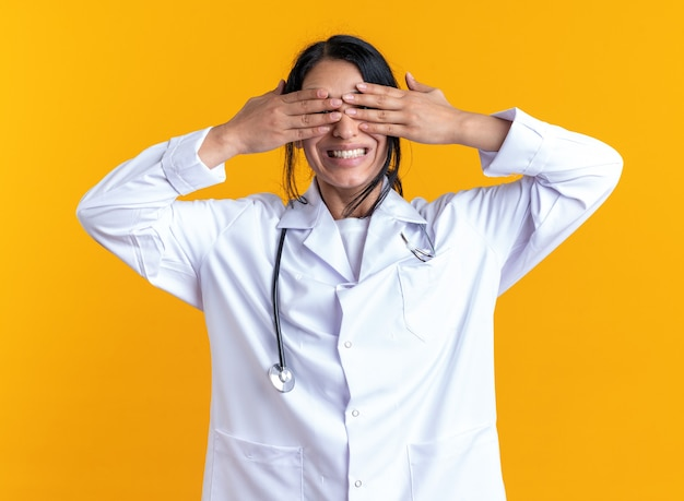 Podekscytowana młoda lekarka nosząca szatę medyczną ze stetoskopem zakrytym okiem z rękami odizolowanymi na żółtej ścianie