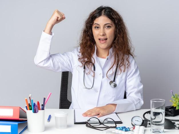 Podekscytowana młoda lekarka ubrana w szatę medyczną i stetoskop, siedząca przy stole z narzędziami medycznymi, trzymając rękę na stole, patrząc na przód, wykonując silny gest na białym tle na białej ścianie
