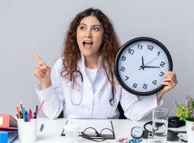 Podekscytowana młoda lekarka ubrana w szatę medyczną i stetoskop siedzący przy stole z narzędziami medycznymi trzymający zegar patrzący i wskazujący na bok na białym tle na białej ścianie