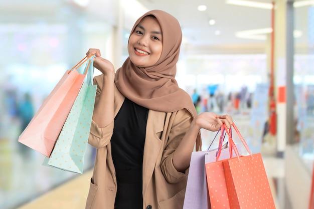 Podekscytowana młoda muzułmańska kobieta na zakupy, trzymając w ręku papierową torbę w centrum handlowym