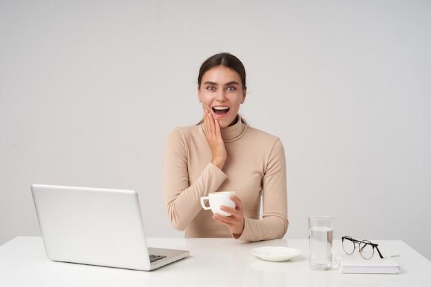 Podekscytowana młoda piękna brunetka kobieta trzyma rękę na policzku i patrzy z szeroko otwartymi oczami i ustami, trzymając filiżankę herbaty, pozując nad białą ścianą