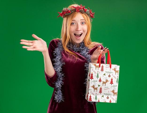 Podekscytowana młoda piękna dziewczyna ubrana w czerwoną sukienkę z wieńcem i girlandą na szyi, trzymając torbę na prezent, rozkładając rękę na białym tle na zielonym tle