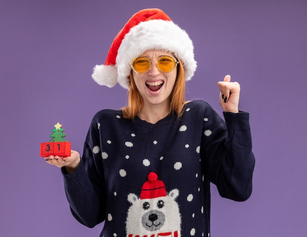Podekscytowana młoda piękna dziewczyna ubrana w świąteczny sweter i kapelusz w okularach trzyma świąteczną zabawkę pokazującą tak gest na białym tle na fioletowym tle