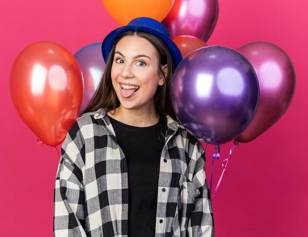 Podekscytowana młoda piękna dziewczyna w imprezowym kapeluszu stojąca przed balonami pokazującymi język na różowej ścianie