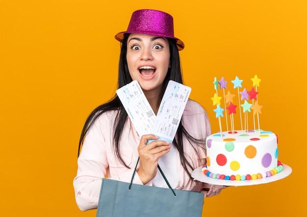 Podekscytowana młoda piękna dziewczyna w kapeluszu imprezowym trzymająca torbę na prezent z ciastem i biletami na pomarańczowej ścianie