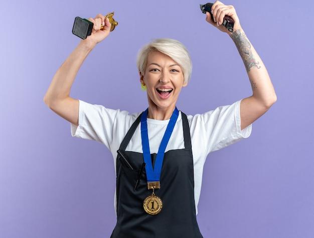 Podekscytowana młoda piękna kobieta fryzjerka w mundurze nosząca medal, trzymająca puchar zwycięzcy z maszynkami do strzyżenia włosów odizolowana na niebieskiej ścianie