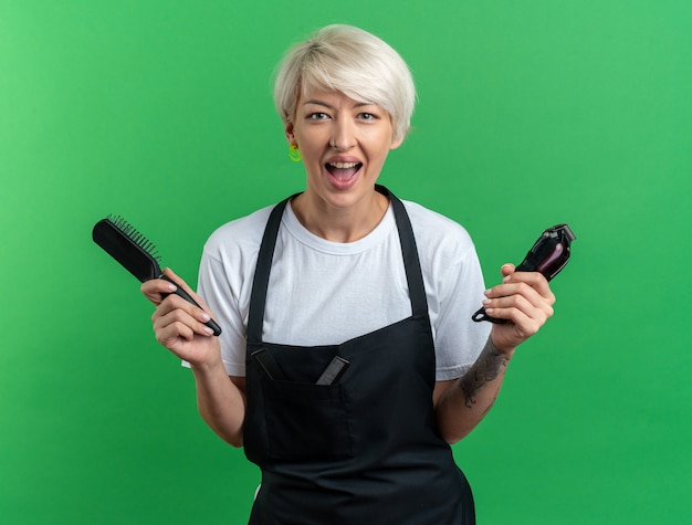 Podekscytowana młoda piękna kobieta fryzjerka w mundurze trzymająca maszynkę do strzyżenia włosów z grzebieniem odizolowanym na zielonej ścianie