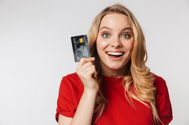 Podekscytowana młoda piękna kobieta pozuje na białym tle nad białą ścianą trzymając kartę kredytową