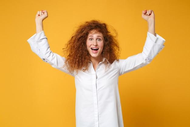 Podekscytowana młoda ruda kobieta dziewczyna w białej koszuli pozuje na białym tle na żółto pomarańczowej ścianie