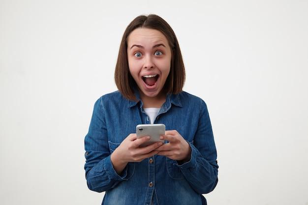 Podekscytowana młoda śliczna ciemnowłosa kobieta z przypadkową fryzurą, patrząc oszołomiony na aparat z szeroko otwartymi ustami, stojąc na białym tle ze swoim smartfonem
