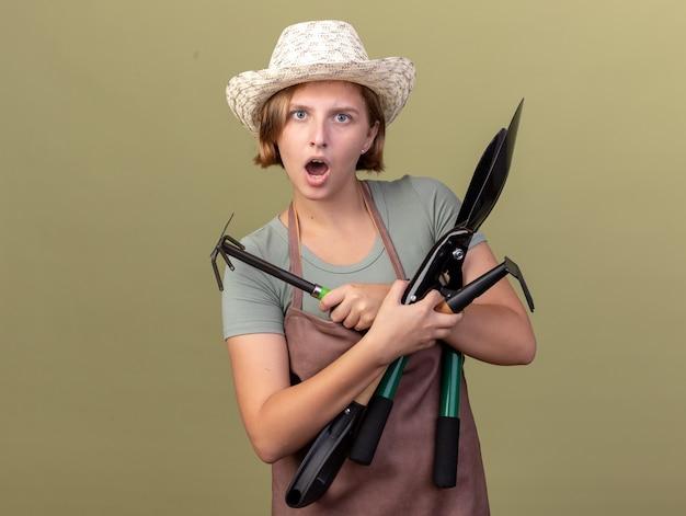 Podekscytowana młoda słowiańska ogrodniczka w kapeluszu ogrodniczym trzymająca narzędzia ogrodnicze