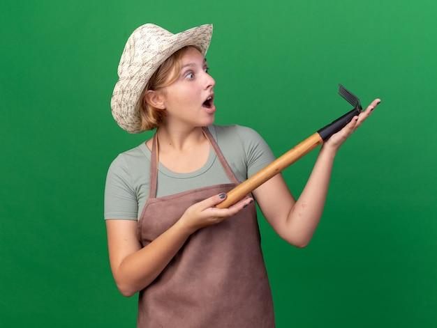 Podekscytowana młoda słowiańska ogrodniczka w kapeluszu ogrodniczym, trzymająca się i patrząca na prowizję