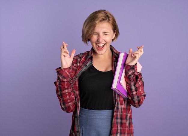 Podekscytowana młoda słowiańska studentka stoi z zamkniętymi oczami, krzyżując palce, trzymając książkę i notatnik