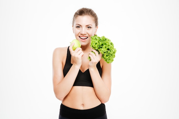Podekscytowana młoda sportowa kobieta trzyma sałatę i zielone jabłko na białym tle