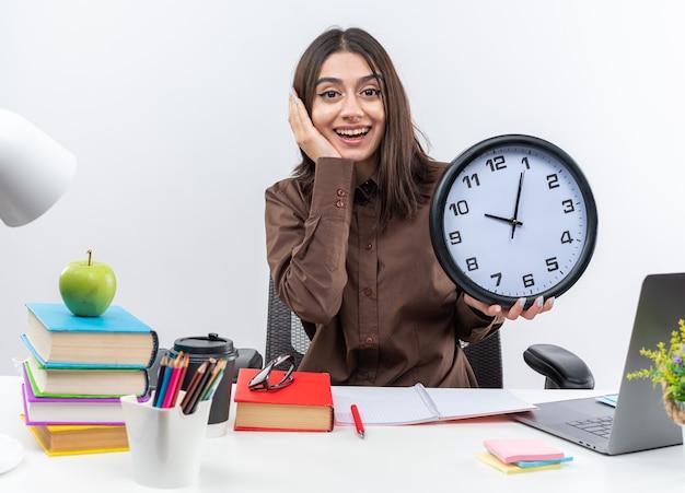 Podekscytowana młoda szkolna kobieta siedzi przy stole z szkolnymi narzędziami, trzymając zegar ścienny, kładąc dłoń na policzku