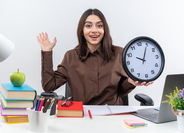 Podekscytowana młoda szkolna kobieta siedzi przy stole z szkolnymi narzędziami trzymającymi zegar ścienny