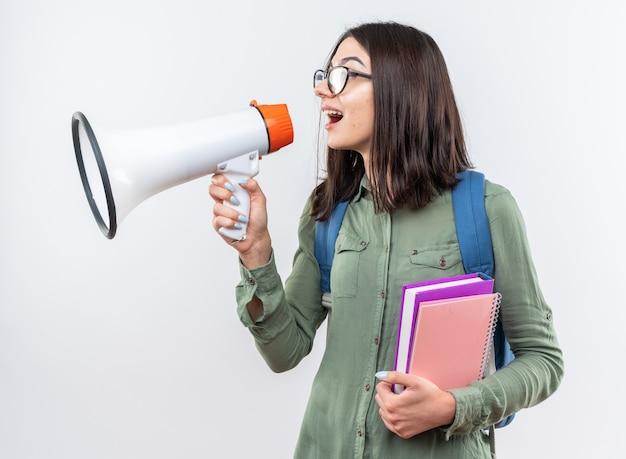 Podekscytowana młoda szkolna kobieta w okularach z plecakiem trzymająca książki mówi przez głośnik