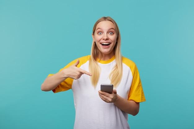 Podekscytowana młoda, urocza blondynka, długowłosa dama z naturalnym makijażem, z zaskoczeniem zaokrąglająca swoje niebieskie oczy, trzymając telefon komórkowy podczas pozowania na niebiesko