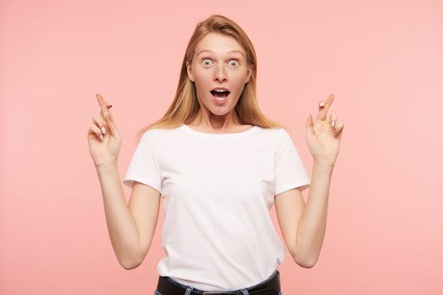 Podekscytowana młoda urocza długowłosa ruda kobieta podnosi ręce ze skrzyżowanymi palcami i patrzy zdumiewająco na aparat z szeroko otwartymi oczami, odizolowana na różowym tle