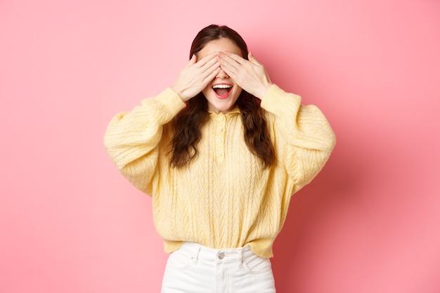 Podekscytowana młoda urodzinowa dziewczyna zasłaniająca oczy, czekająca na niespodziankę stojąca z zawiązanymi oczami na różowej ścianie
