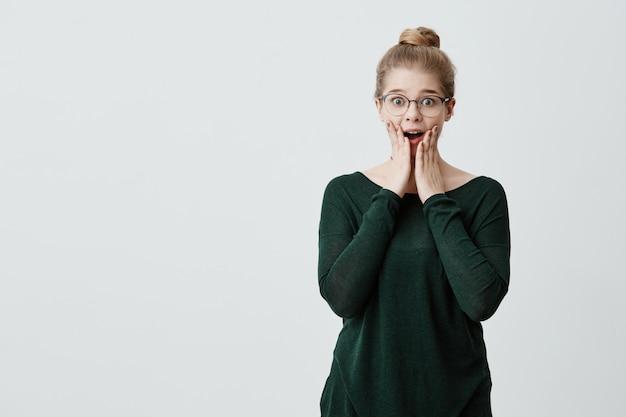 Podekscytowana modelka o blond włosach z węzłem włosów i stylowymi okularami wpatruje się w niewiarygodne spojrzenie, zaskoczona otrzymaniem niespodziewanego prezentu od krewnych. ludzie, wyraz twarzy, pojęcie emocji