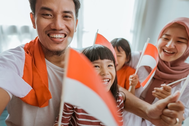 Podekscytowana muzułmańska azjatycka rodzina robi selfie i wideorozmowy przy użyciu telefonu w domu, trzymając flagę indonezyjską