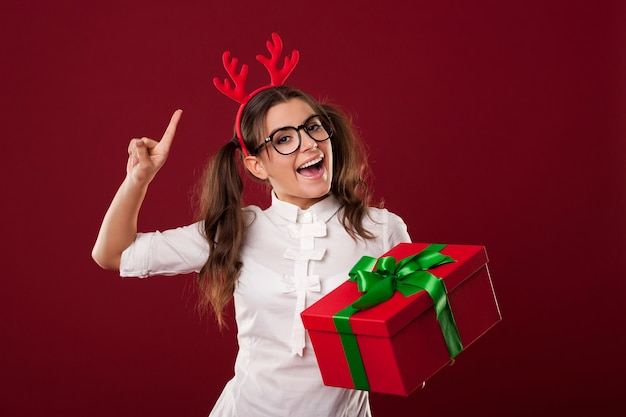 Podekscytowana nerdy kobieta z czerwonym prezentem bożonarodzeniowym