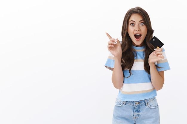 Podekscytowana nowoczesna, modna kobieta, która lubi robić zakupy online, mieć pomysł, podnosić palec wskazujący gest eureki, doskonała sugestia, pamiętaj, co chce kupić, trzymaj kartę kredytową, dysząc, rozbawiony, zafascynowany